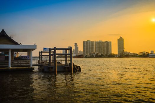 Landscape view of Chao Phraya river at Bang Krachao district pier during sunset  with hi-rise building and blue sky background. Peaceful river pier in Bangkok, Thailand.