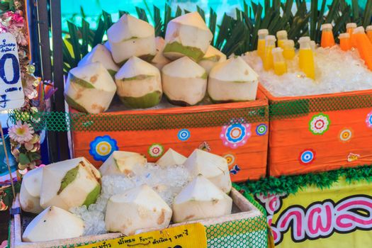 Chiang Mai, Thailand - May 3, 2017: Peeled young coconuts on ice box were displayed for sale as coconut juice at street food stall with price tag.