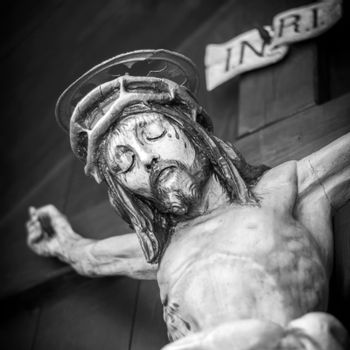 The bleeding body of Jesus Christ, crucified on a wooden cross. Shallow depth of field.