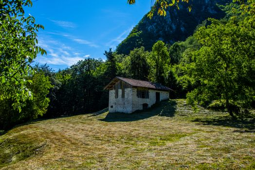 typical tool shed in the alps with freshly cut grass meadows at Lake Ledro in Trento, Italy