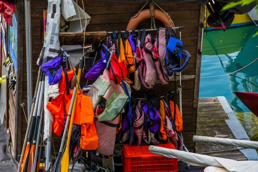colorful life jackets hanging on the wooden shed at Lake Ledro in Trento, Italy