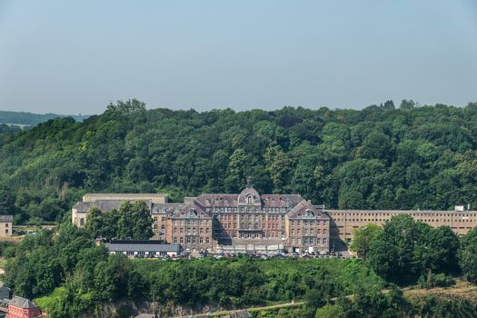 Dinant, Belgium - June 26, 2019: Seen from Citadelle. Large building is College Notre Dame de Bellevue, school system from primary to high school. Forests in back. Light blue sky.
