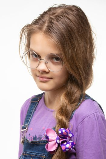 Portrait of a girl of eleven in round glasses and a long braid