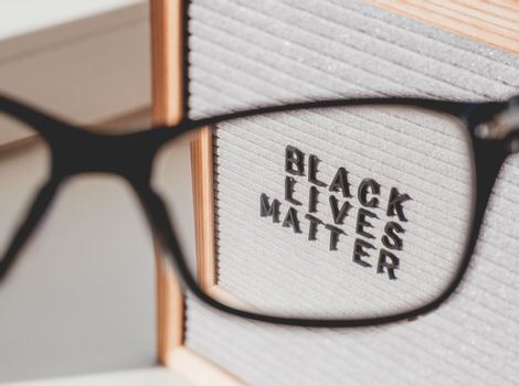 View on letterboard with words Black Lives Matter through eyeglasses. Concept with actual statement. Social issue. Closer look on race problem in society.
