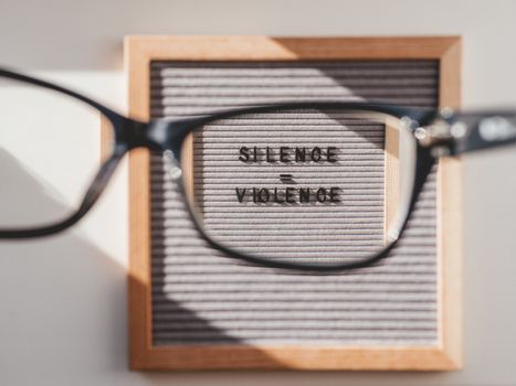 Top view on letter board with words Silence equal Violence through eyeglasses. Flat lay concept with actual statement. Social issue. Race problem in society.