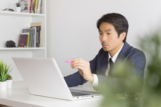 Asian Financial Advisor or Asian Consulting Businessman Seriously Customer Recommend in front of Laptop. Asian financial advisor or Asian consulting businessman contact with customer via internet