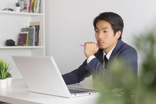 Asian Financial Advisor or Asian Consulting Businessman in Suit Seriously Thinking in front of Laptop. Asian financial advisor or Asian consulting businessman contact with customer via internet