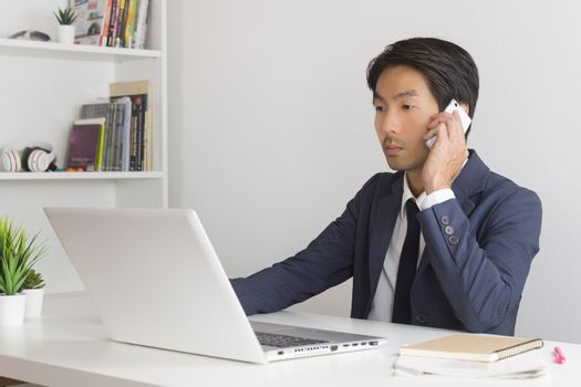 Asian Financial Advisor or Asian Consulting Businessman in Suit Talking with Customer by use Smartphone and Laptop. Asian Financial Advisor or Asian Consulting Businessman working in office