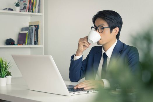 Asian Businessman Wear Eyeglasses and Drink Coffee in front of Laptop. Relax between working time of Asian businessman