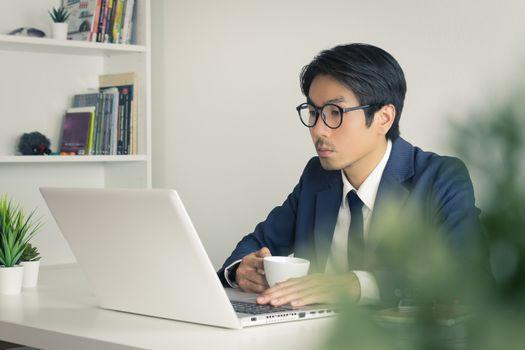 Asian Businessman Wear Eyeglasses Seriously Analyze Financial Data in Laptop. Asian businessman working in office
