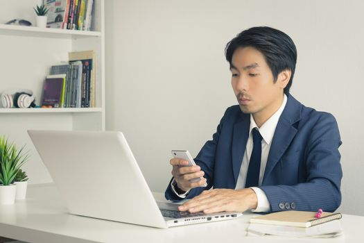 Asian Financial Advisor or Asian Consulting Businessman Sending Message or Chat with Customer. Asian Financial Advisor or Asian Consulting Businessman use smartphone in office