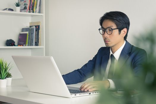 Asian Financial Advisor or Asian Consulting Businessman Seriously Working in front of Laptop. Asian financial advisor or Asian consulting businessman working in office