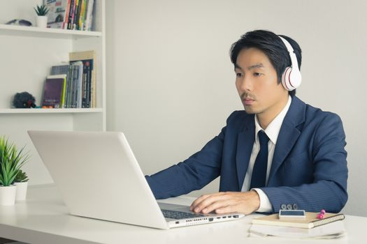 Asian Man Call Center in Suit Wear Headset or Headphone Contacting and Service the Customer Via Internet in Office. Asian man call center working with laptop