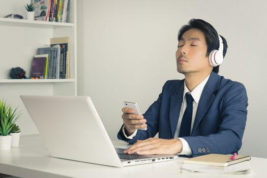 Asian Businessman in Suit Wear Headphone Listen to Music by Bluetooth Technology in Smartphone. Relax time of Asian businessman in office