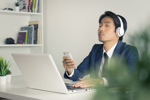 Asian Businessman Listen to Music by Headphone with Tree Foreground. Relax time of Asian businessman in office