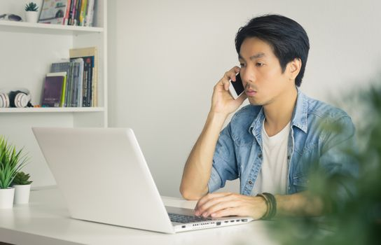 Portrait Asian Casual Businessman in Denim or Jeans Shirt Using Laptop and Smartphone in Home Office. Casual businessman working with technology
