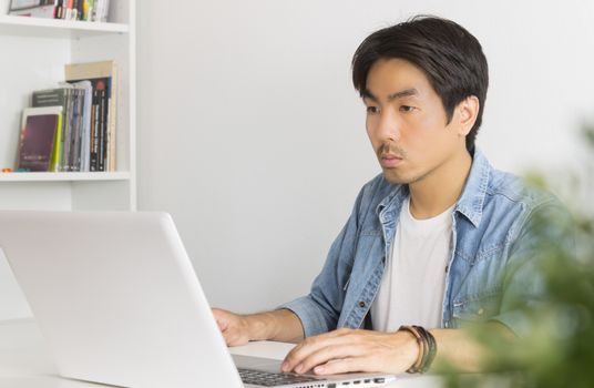 Young Asian Casual Businessman Working with Laptop at Workplace in Home Office. Casual business or informal business in home office