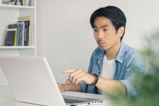 Young Asian Casual Businessman Pointing Laptop Monitor at Workplace in Home Office. Casual business or informal business in home office
