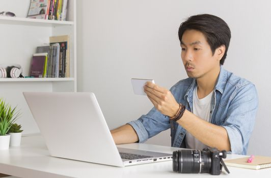 Asian Photographer or Freelancer in Denim or Jeans Shirt Checking Photo File by Smartphone in front of Laptop in Home Office. Photographer or freelancer working with technology