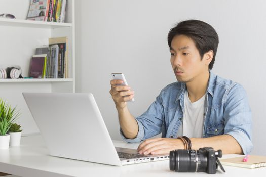 Asian Photographer or Freelancer in Denim or Jeans Shirt Send Message to Customer by Smartphone in front of Laptop in Home Office. Photographer or freelancer working with technology
