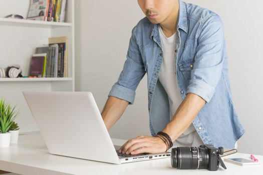 Asian Photographer or Freelancer in Denim or Jeans Shirt Working with Laptop in Standing Posture in Home Office. Photographer or freelancer working with technology