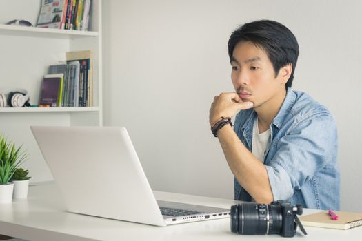 Asian Photographer or Freelancer in Denim or Jeans Shirt Serious Thinking in front of Laptop in Home Office. Photographer or freelancer working with technology