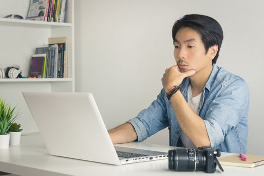 Asian Photographer or Freelancer in Denim or Jeans Shirt Serious Checking Photo File in Laptop in Home Office. Photographer or freelancer working with technology