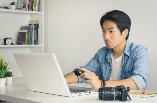 Asian Photographer or Freelancer in Denim or Jeans Shirt Checking Media File in Action Camera with Laptop in Home Office. Photographer or Freelancer working with technology