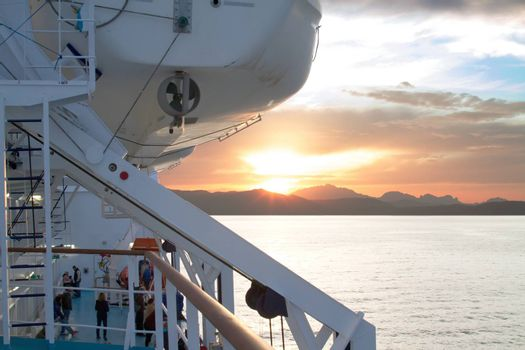 Sunrise on the Sardinian sea coast with intense orange color seen from the sea on the ferry that is about to dock and people on board