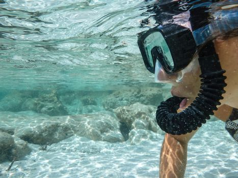 Close up of the face of a young woman in bikini with mask and snorkel shooting underwater in the crystal clear sea with white sand and rocks on the bottom