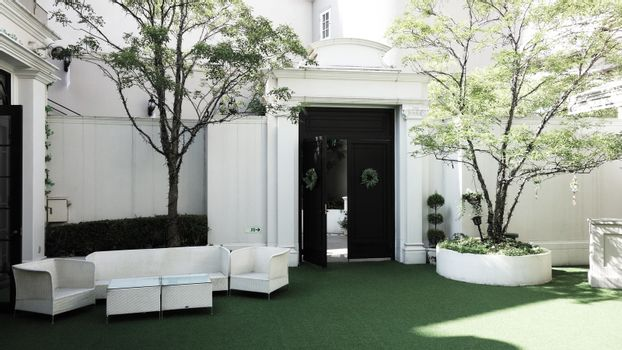 interior Luxury living space outdoor lounge area in the garden, white sofa and table and white chair in the garden at cefe restaurant