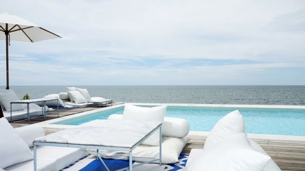 Swimming pool looking at blue sea view and blue sky background. Relax vacation time with nice place at sea beach