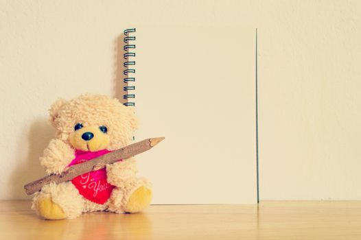 Teddy bear with pen and blank notebook filtered image