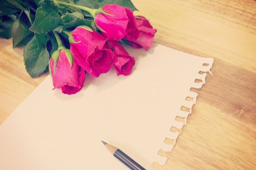 Vintage,retro of note book paper and pencil with rose on wooden background soft focus.