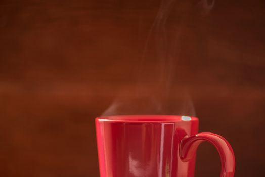 red coffee cup with smoke stream on wooden table under moring sunlight.