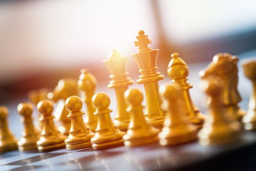 gold chess pieces on a chessboard, business strategy concept