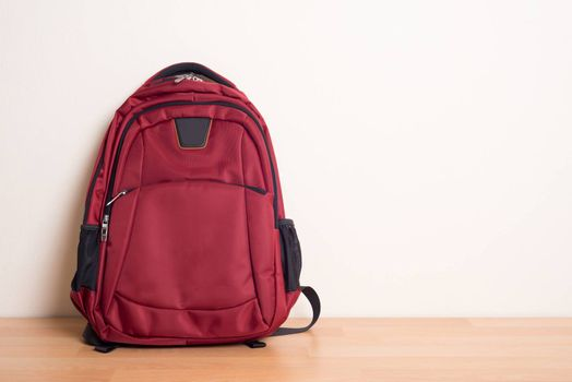 red school bag on wood table.