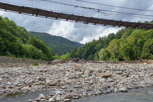 Suspension bridge over the mountain river