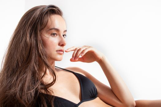 Attractive sporty woman in black bikini posing on white background. Photo of brunette woman with slim toned body. Beauty and body care concept. bikini woman in front of white wall