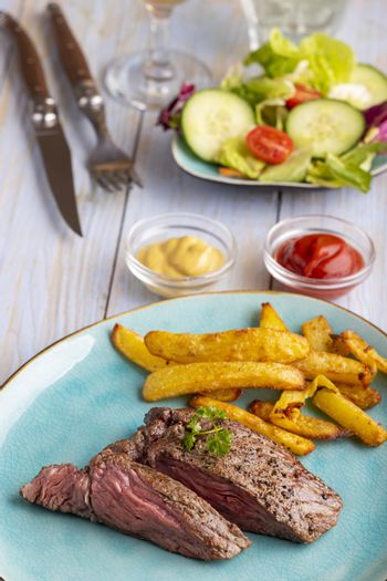 steak on a plate with french fries