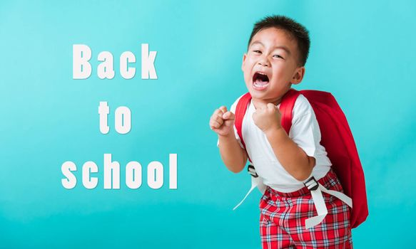Back to school. Portrait happy Asian cute little child boy in uniform smile raise hands up glad when go back to school, isolated blue background. Kid from preschool kindergarten with school backpack