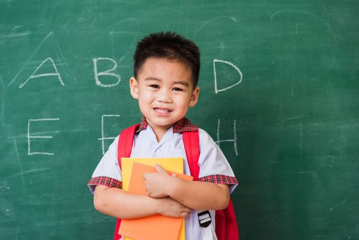 Back to School. Happy Asian funny cute little child boy kindergarten in student uniform with school bag and books smile show finger thumb up on green school blackboard, First time to school education