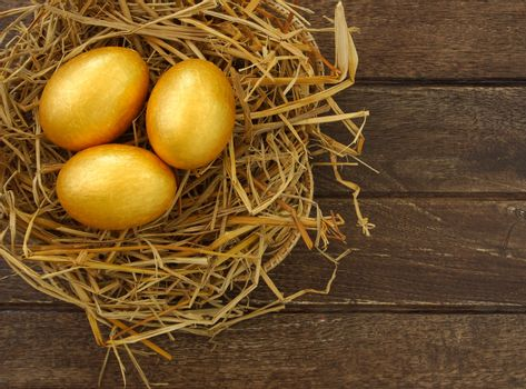 gold eggs in nest on wood background ,business concept