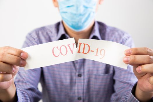 man wearing protective medical surgical face mask and tearing a paper with the words of covid 19