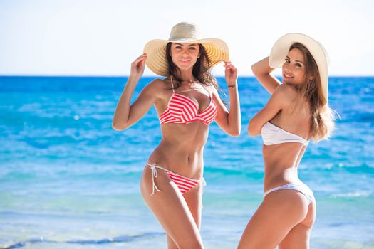 Two female friends in bikini and sunhat on tropical sea beach at vacation