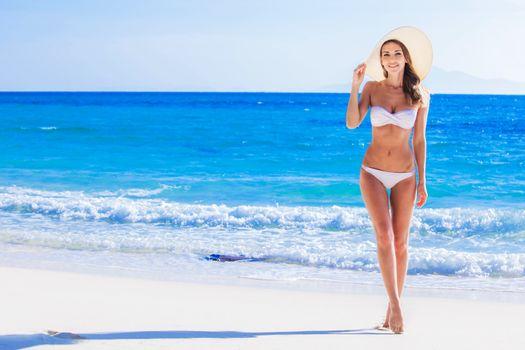 Happy smiling young woman in bikini and sunhat on sea beach