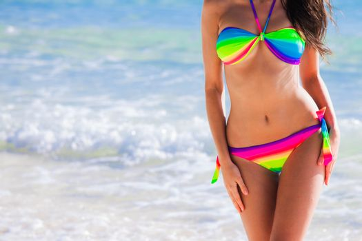 Woman with perfect body in rainbow bikini over blue sea background