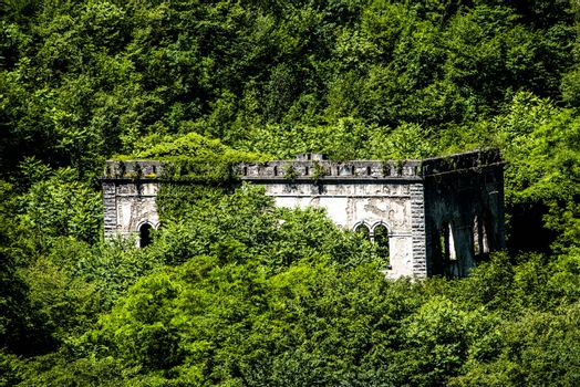 old power plant long abandoned and covered by luxuriant vegetation near Lake Ledro in Trento, Italy