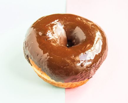One chocolate donut on a light blue and pink background, top view.