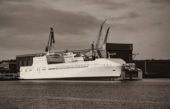 Cargo and passenger ferry in the harbor. Shipyard on the background.